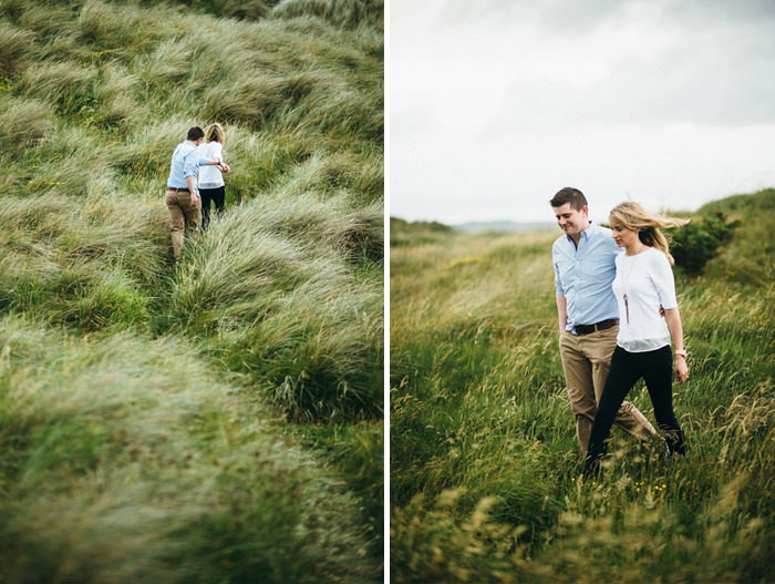 sarah and Ross walking on grass during engagement session in Sligo