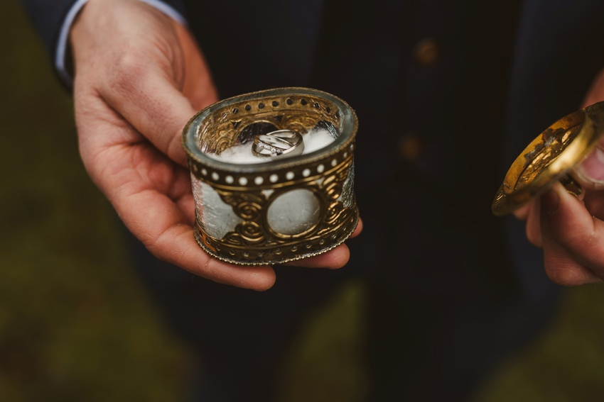groom holding wedding rings