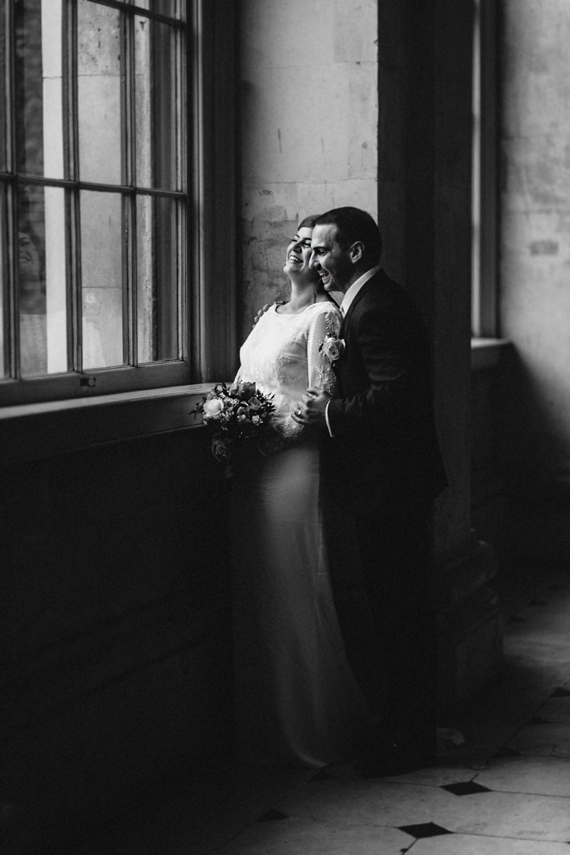 Bride and Groom beside big victorian window in Dublin City Hall smiling during their photoshot  at wedding