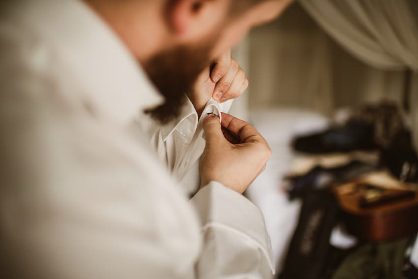 cufflinks put into shirt by irish groom