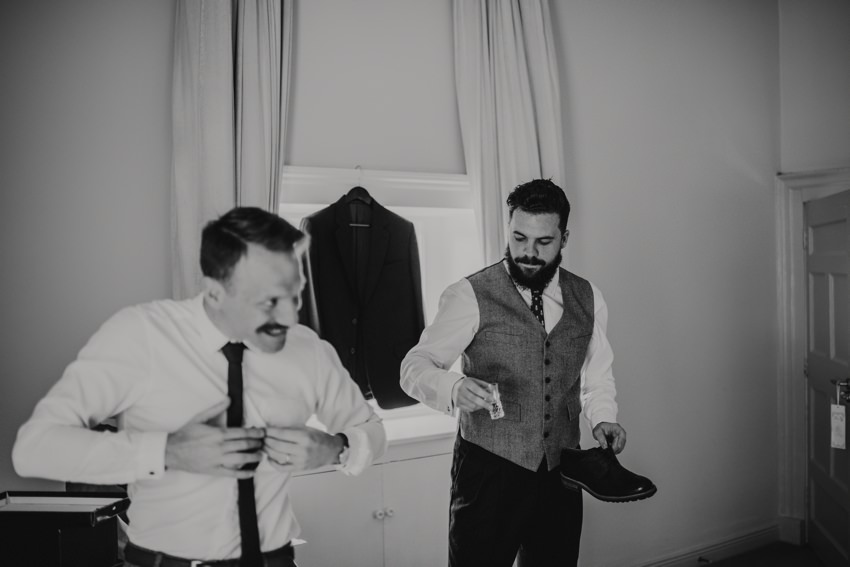 groomsman joking with groom at wedding