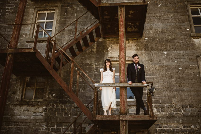 bride and groom at industrial old stairs in Ireland