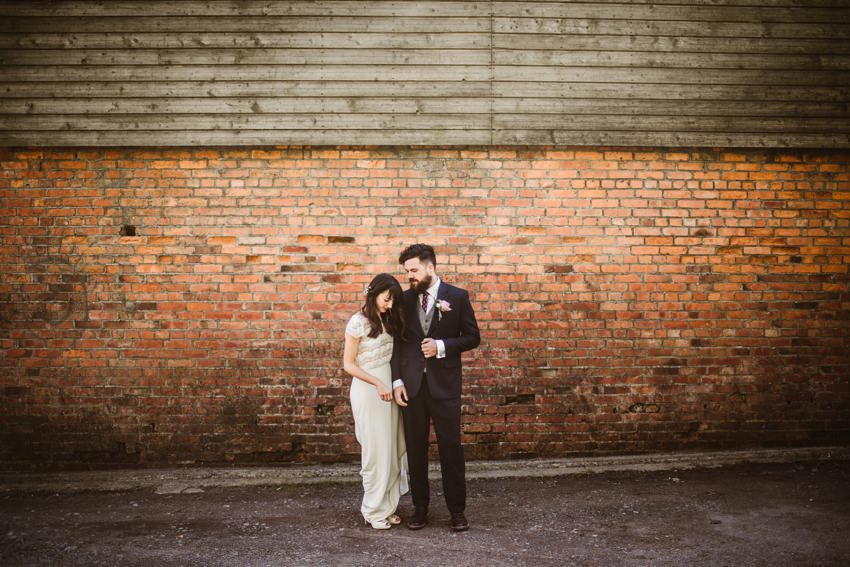 married couples at front of red brick wall in millhouse slane