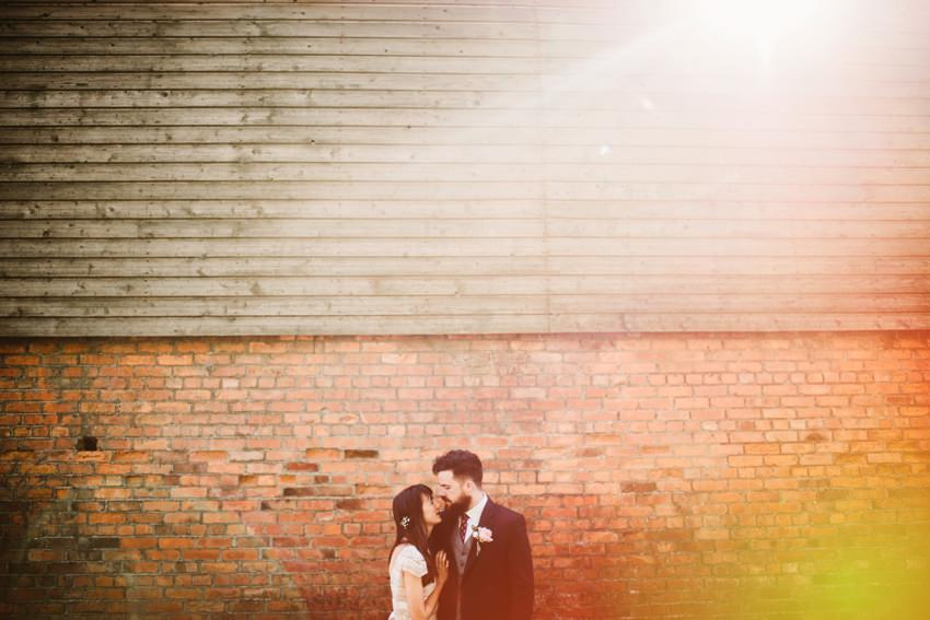 photographs of married couple at front of red brick wall at The Millhouse Slane with sunset