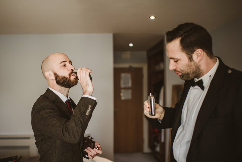 groom drinking irish whiskey from the hip flask