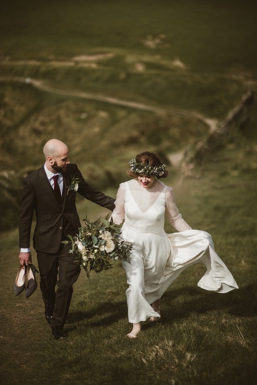 wedding couples walking on cliffs in doolin. groom wearing brown tweed suite and bride white dress and flower crown on head
