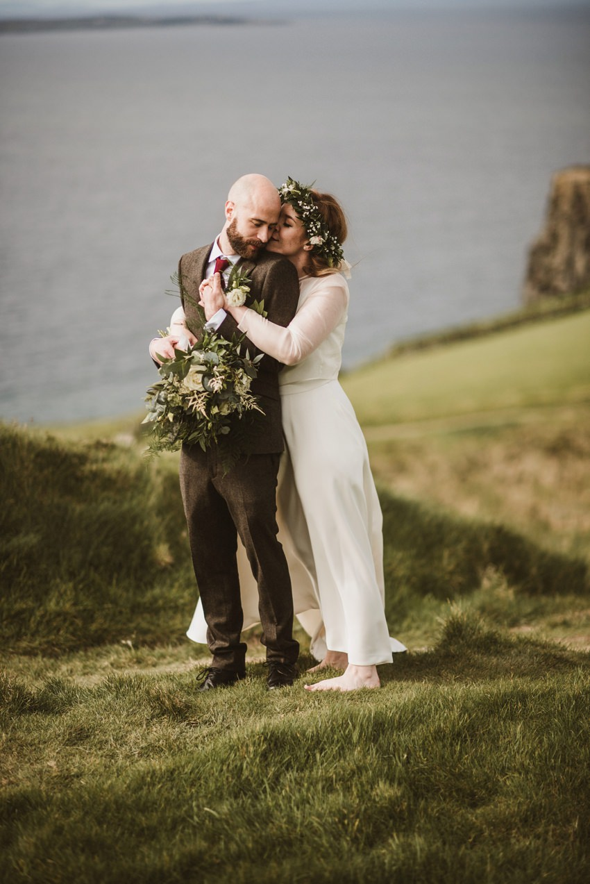 bride with flower crown standing at edge of cliffs of mother in co.clare ireland . wedding in hotel doolin