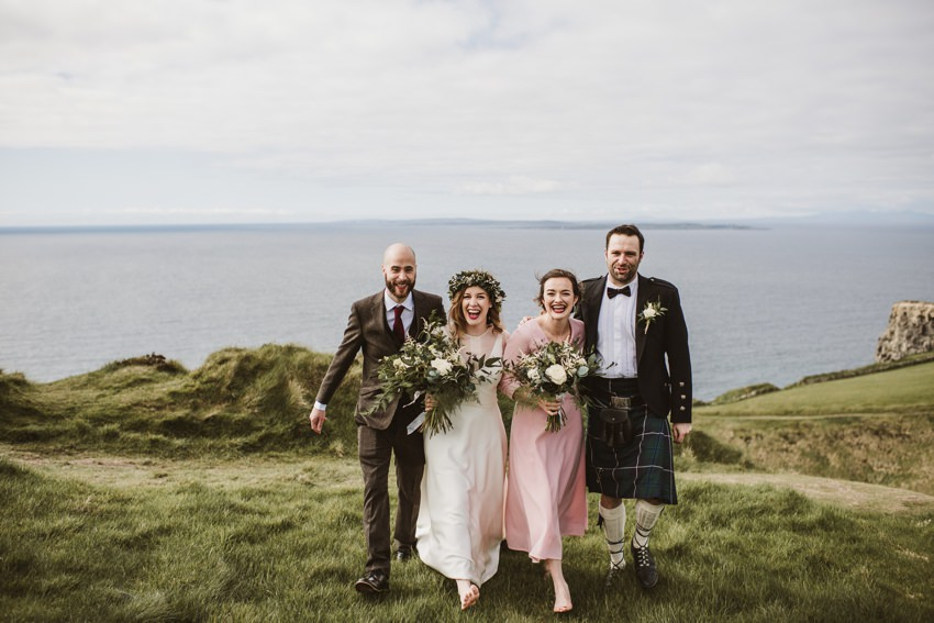 bride ,groom, bridesmaid and groomsman having a fun at cliffs in Ireland when photos are taken by Darek Novak