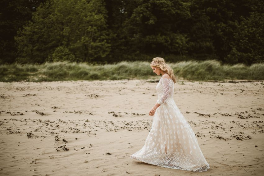 married girl walking barefoot on beach in white boho dress