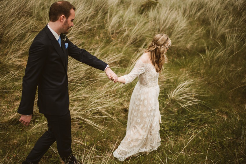bride leading groom thorough long gras to near beach in rathmullan house