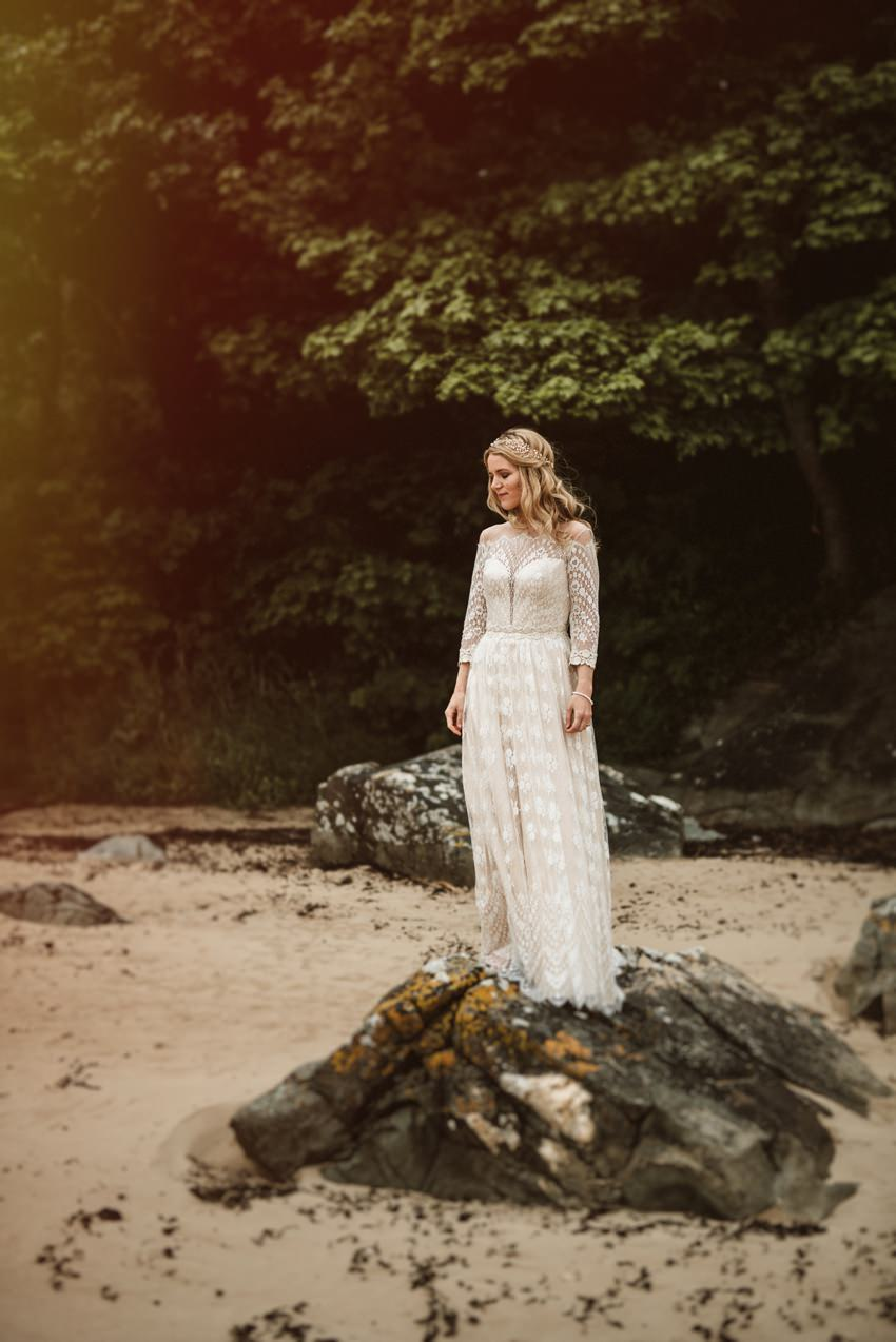 bohemian bride with long blond hair standing on rock at beach in donegal