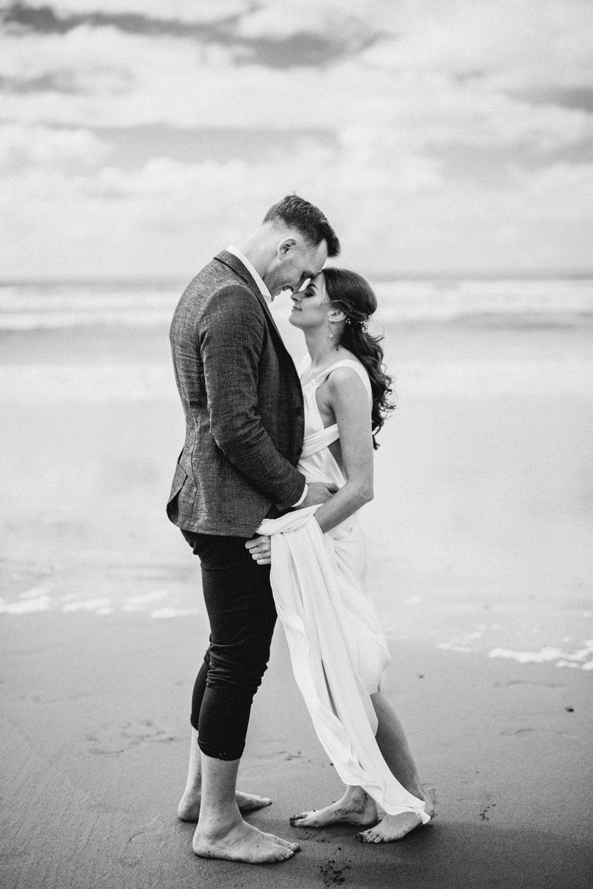 black and white photo of bride barefoot on beach