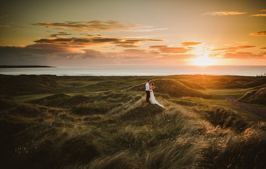beautiful sunset photo of married couples at cliffs in Ireland