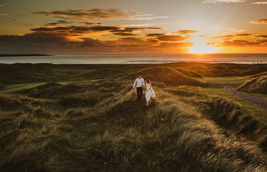 couple in love walking at cliffs at atlantic ocean in ireland