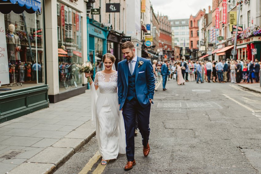 couples walking on dublin street from ceremony