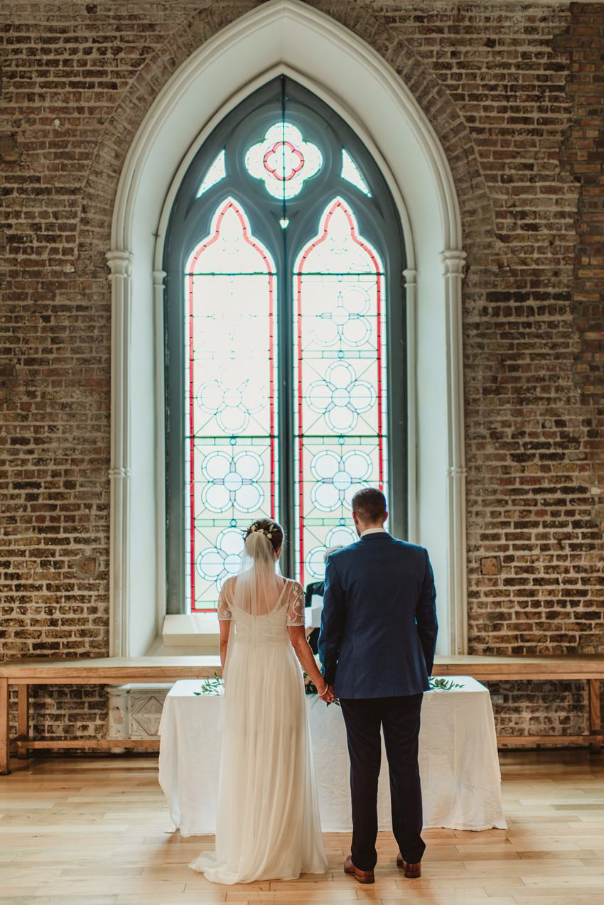 couple standing at front of stained glass in smock alley thetre Dublin