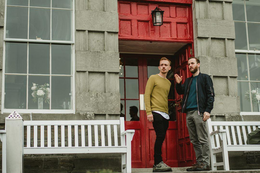 groom at front of red door in bellinter house