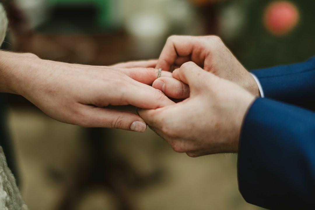 groom putting ring on bride finger