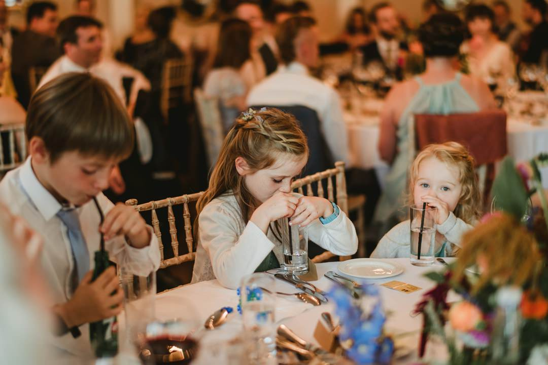 kids at the wedding sit beside table