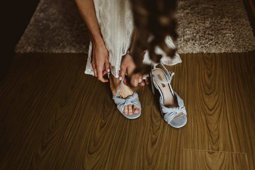 bride puting wedding shoes on feet