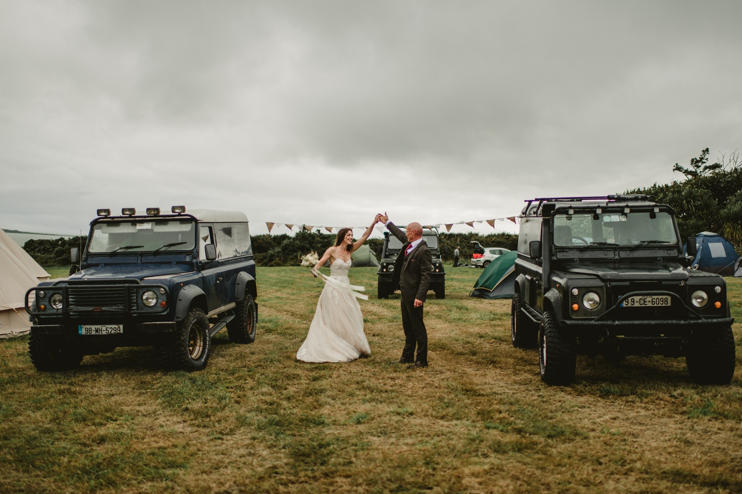 couples dancing between two landrovers