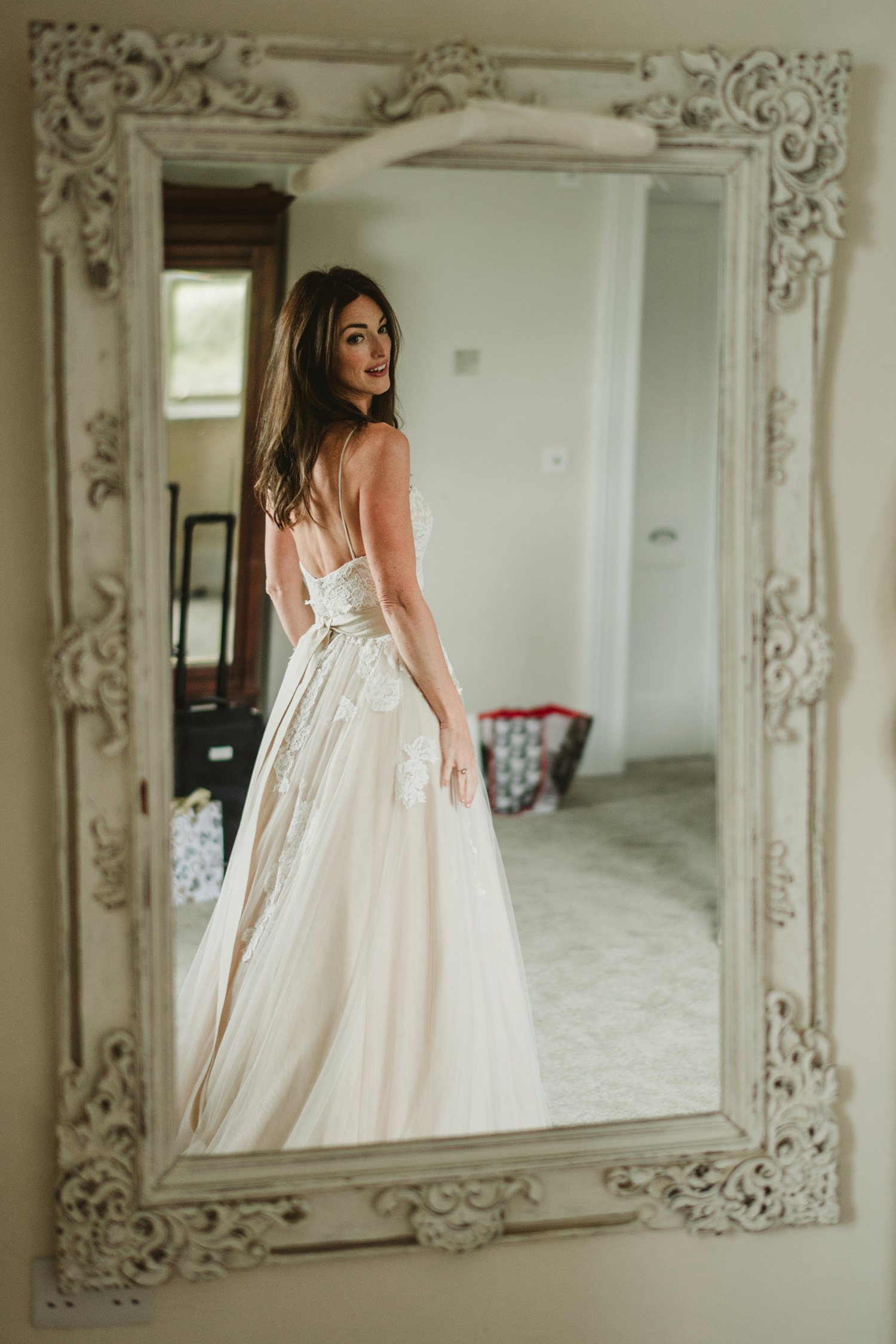 bride checking dress in mirror