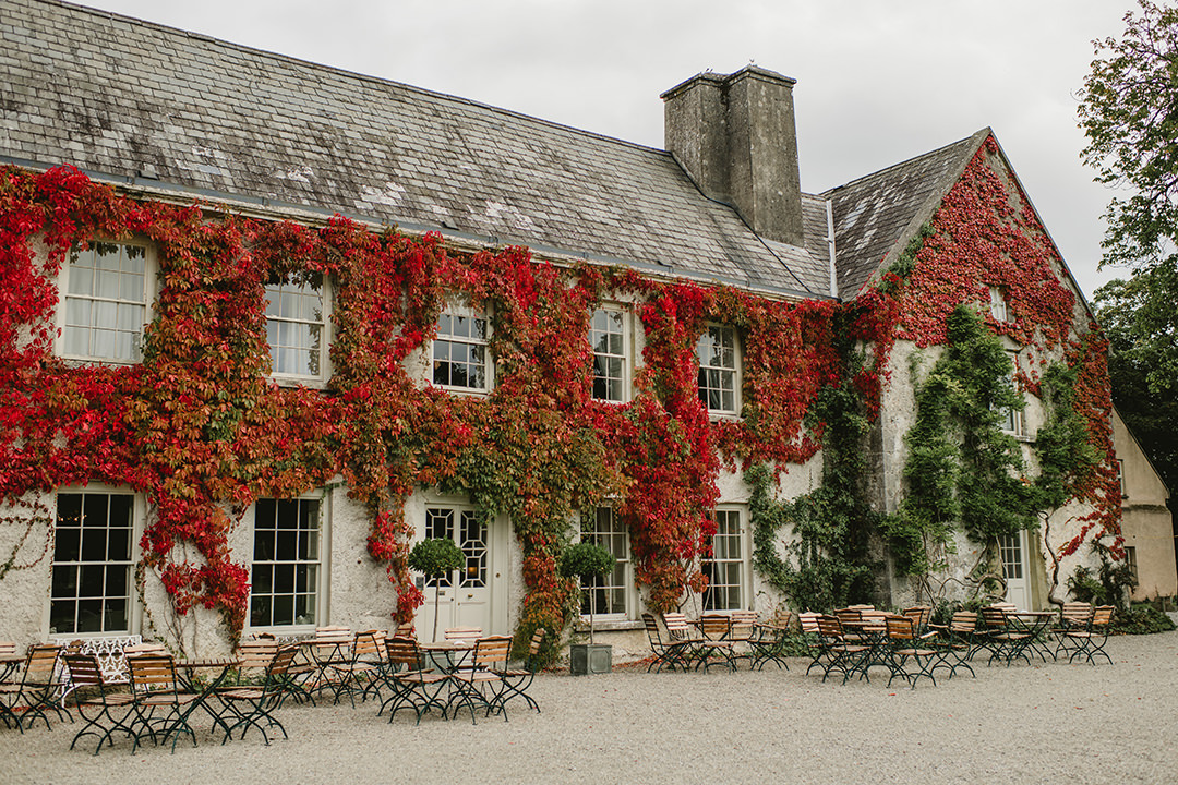 front of beautiful Cloughjordan House during  Autumn Wedding covered with red leaves