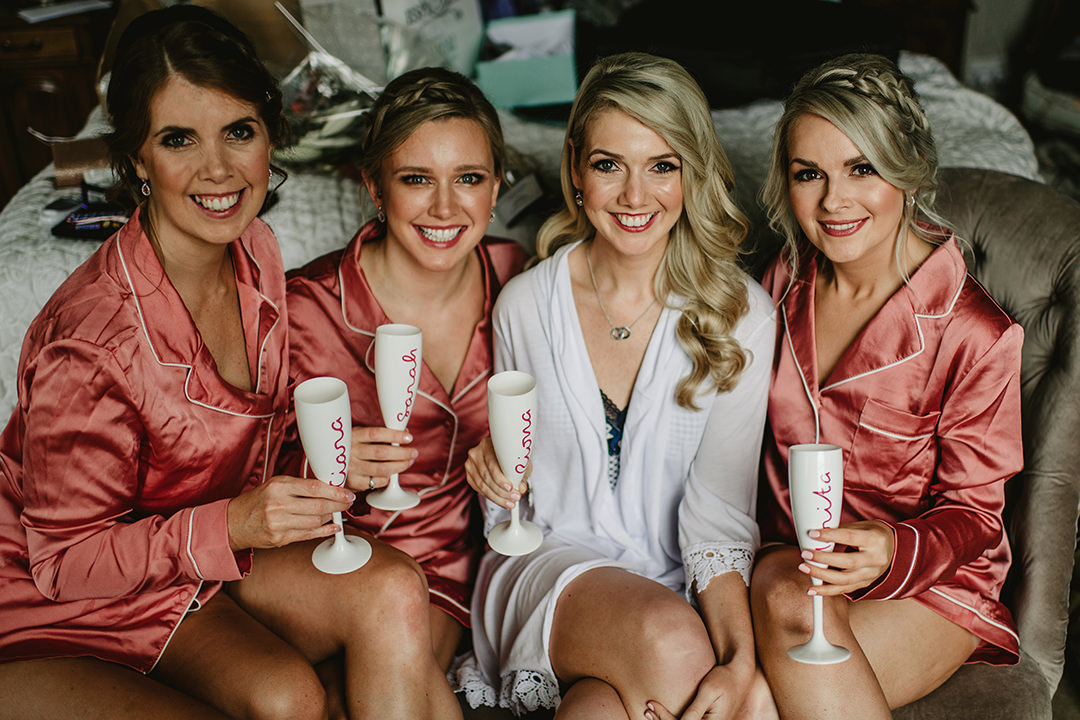 bridesmaids sitting on couch with proseco in hand