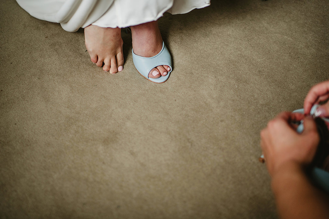 bride putting her wedding shoes on feet
