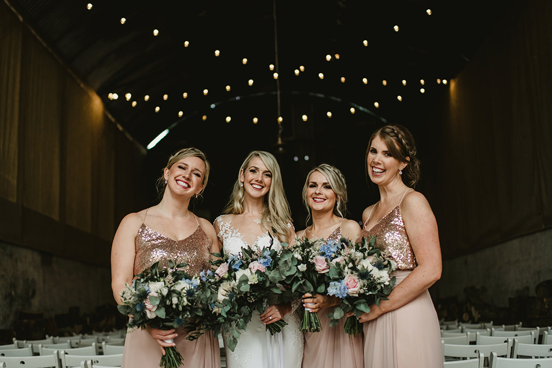 bridesmaids and bride laughing in barn