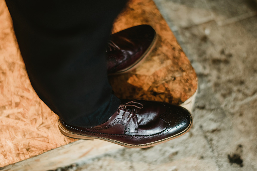 groom shiny shoes in dark burgundy colour
