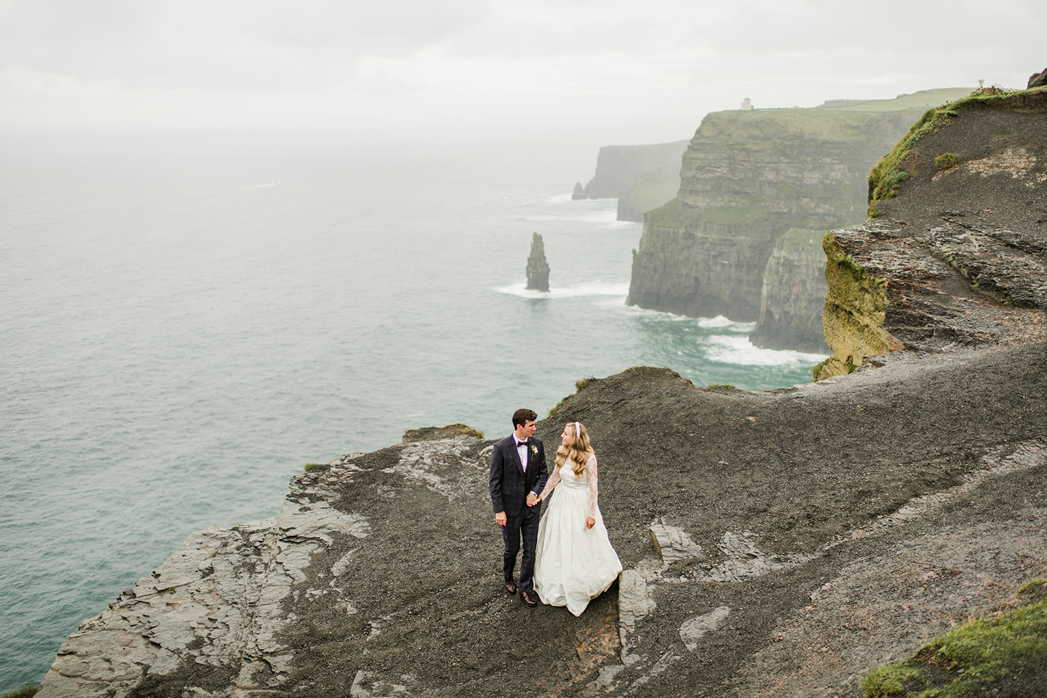 wedding picture with bride and groom and cliffs of moher and ocean in background