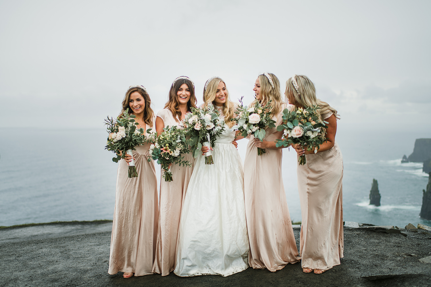 bridesmaids in beautiful boho dresses lough at edge of cliffs in Ireland
