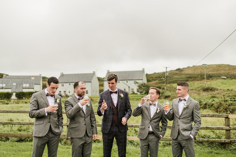 groom and groomsman drink irish whiskey before ceremony in hotel doolin