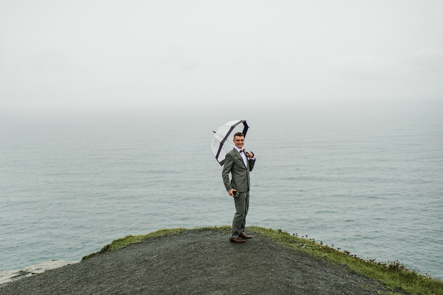 one of the groomsman pose at cliffs of Moher