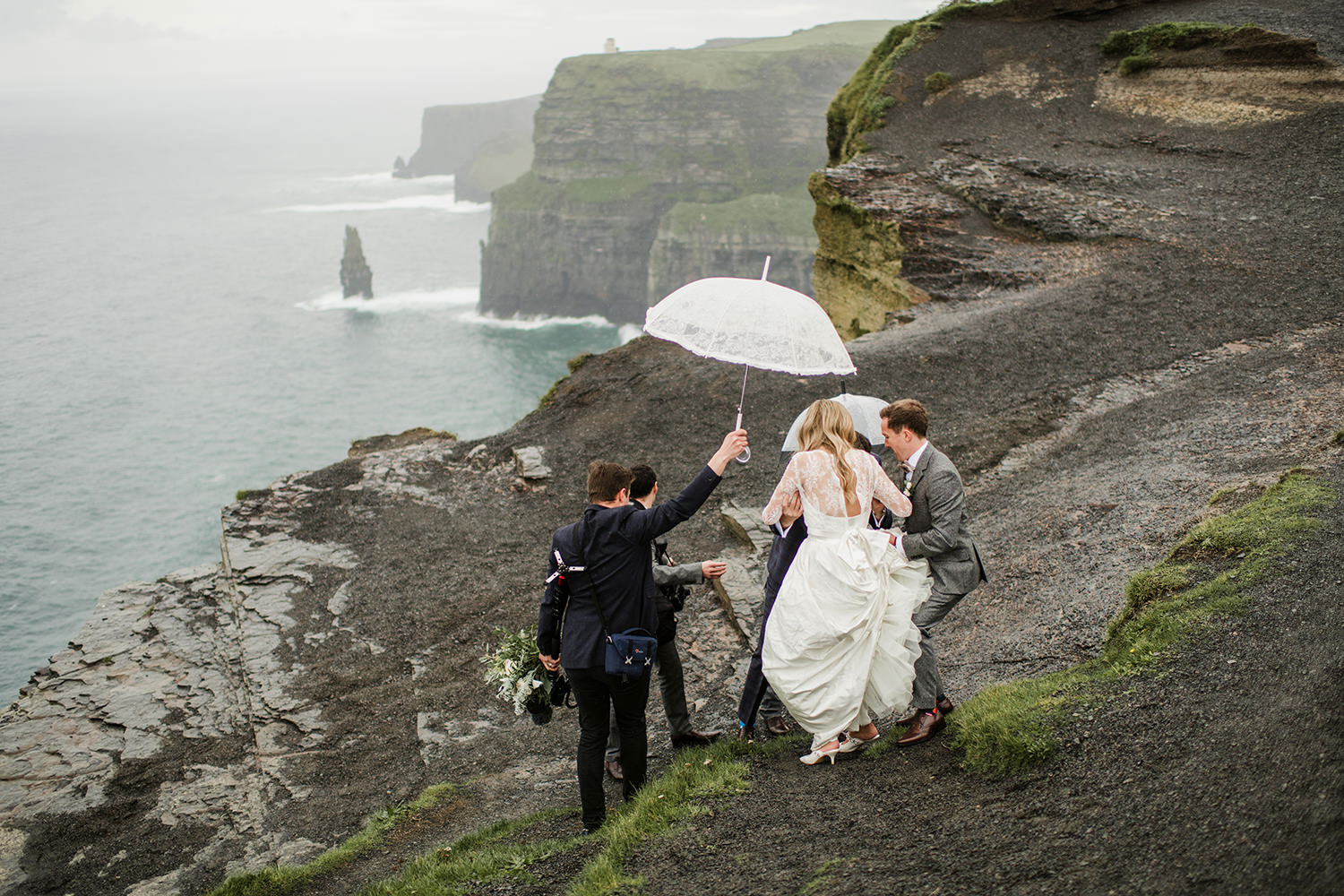 wedding at cliffs of moher bride and groom walking carefuly at the edge of cliffs