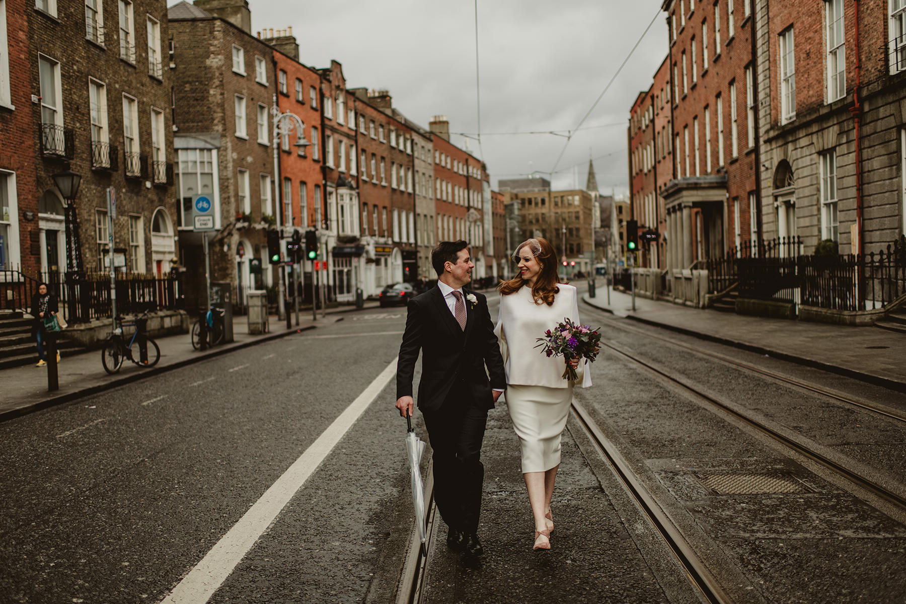 Happy bride and groom walk on Dublin street photographer by Darek Novak