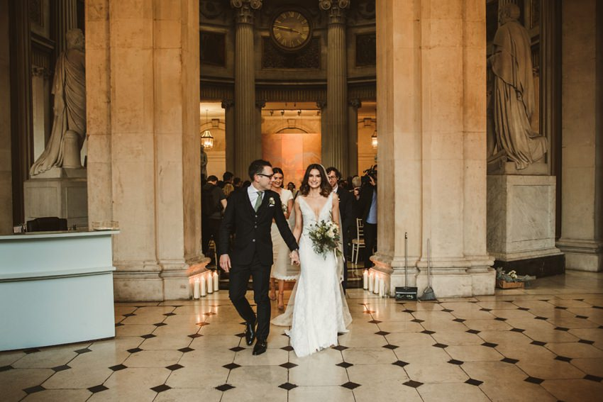 bride and groom walking thorough city hall dublin