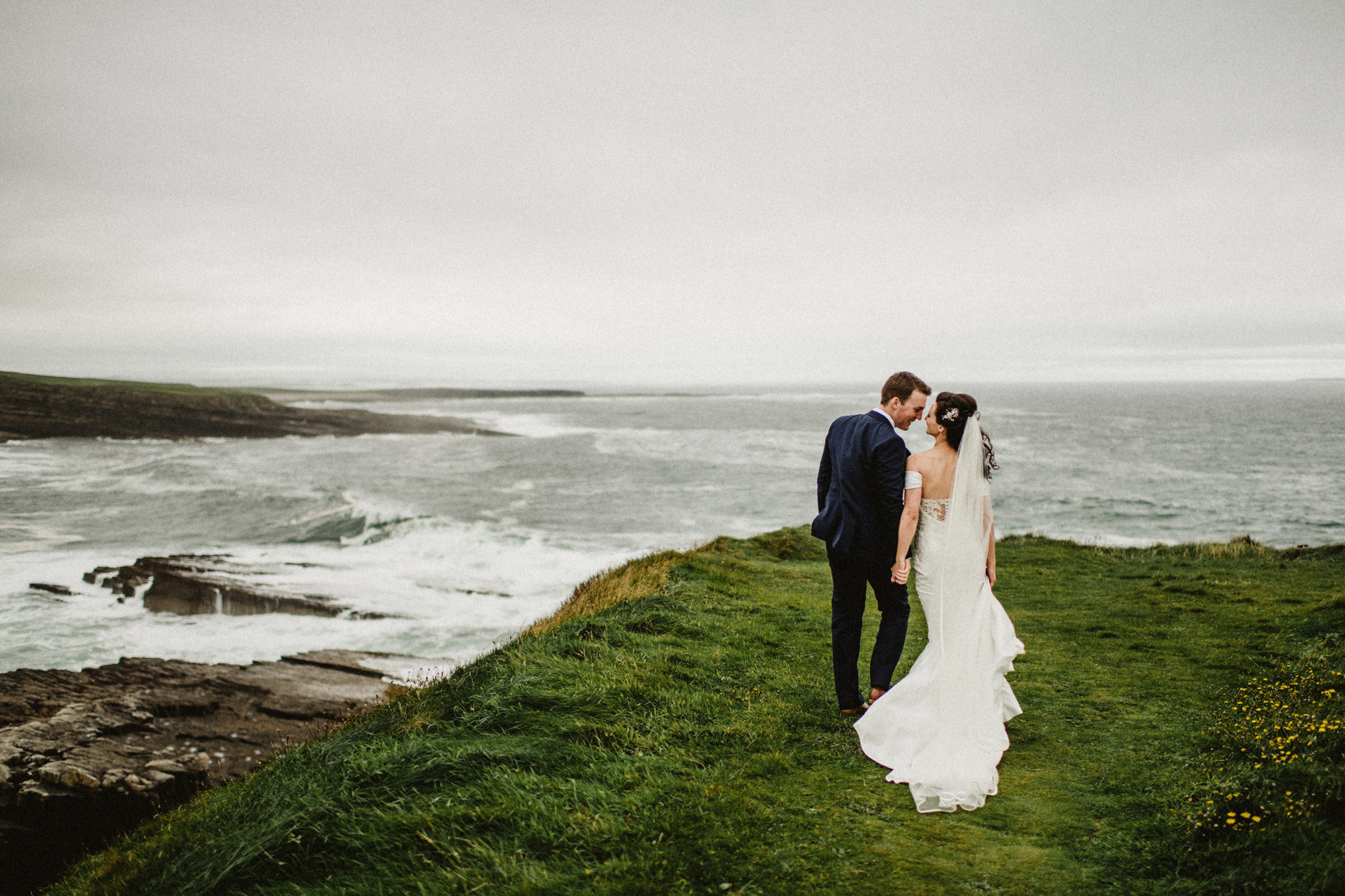 just married couples walk on cliff by Atlantic ocean in North West of Ireland Co.Sligo