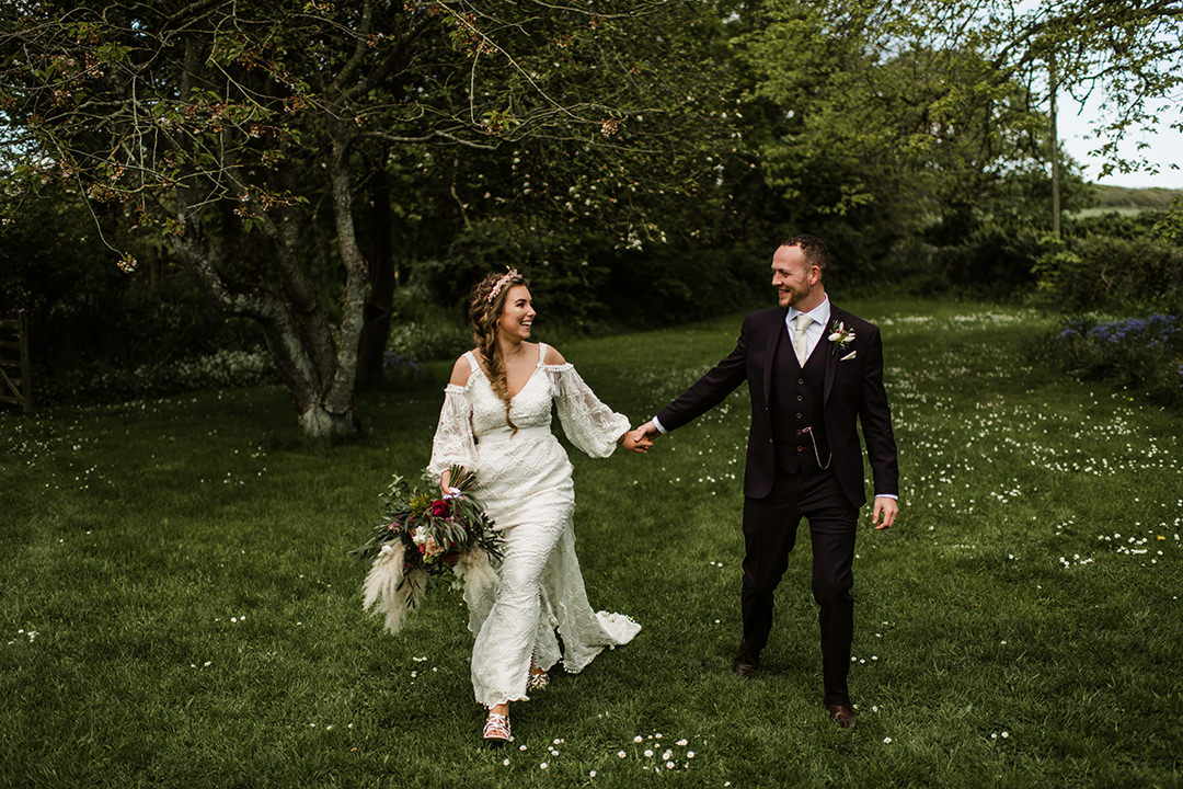 bride and groom walk on grass