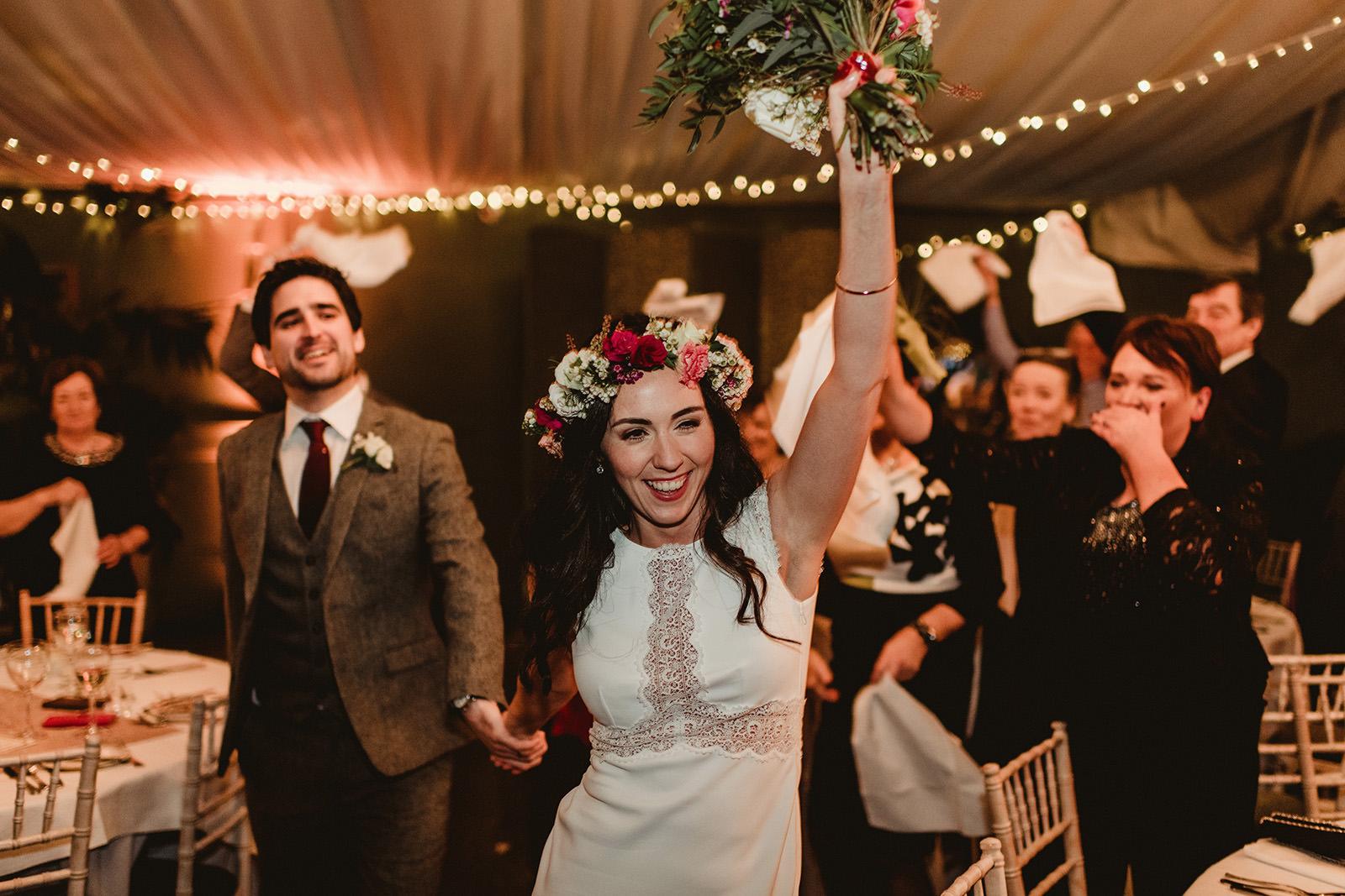 happy bride wearing flower crown walk into pavilon for dinner