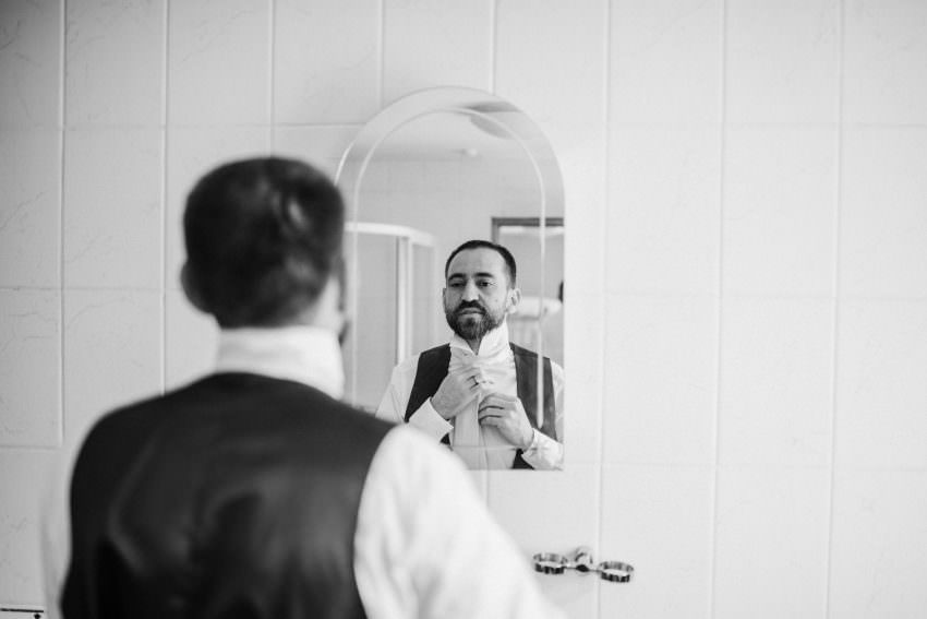 groom fixing tie at front of mirror