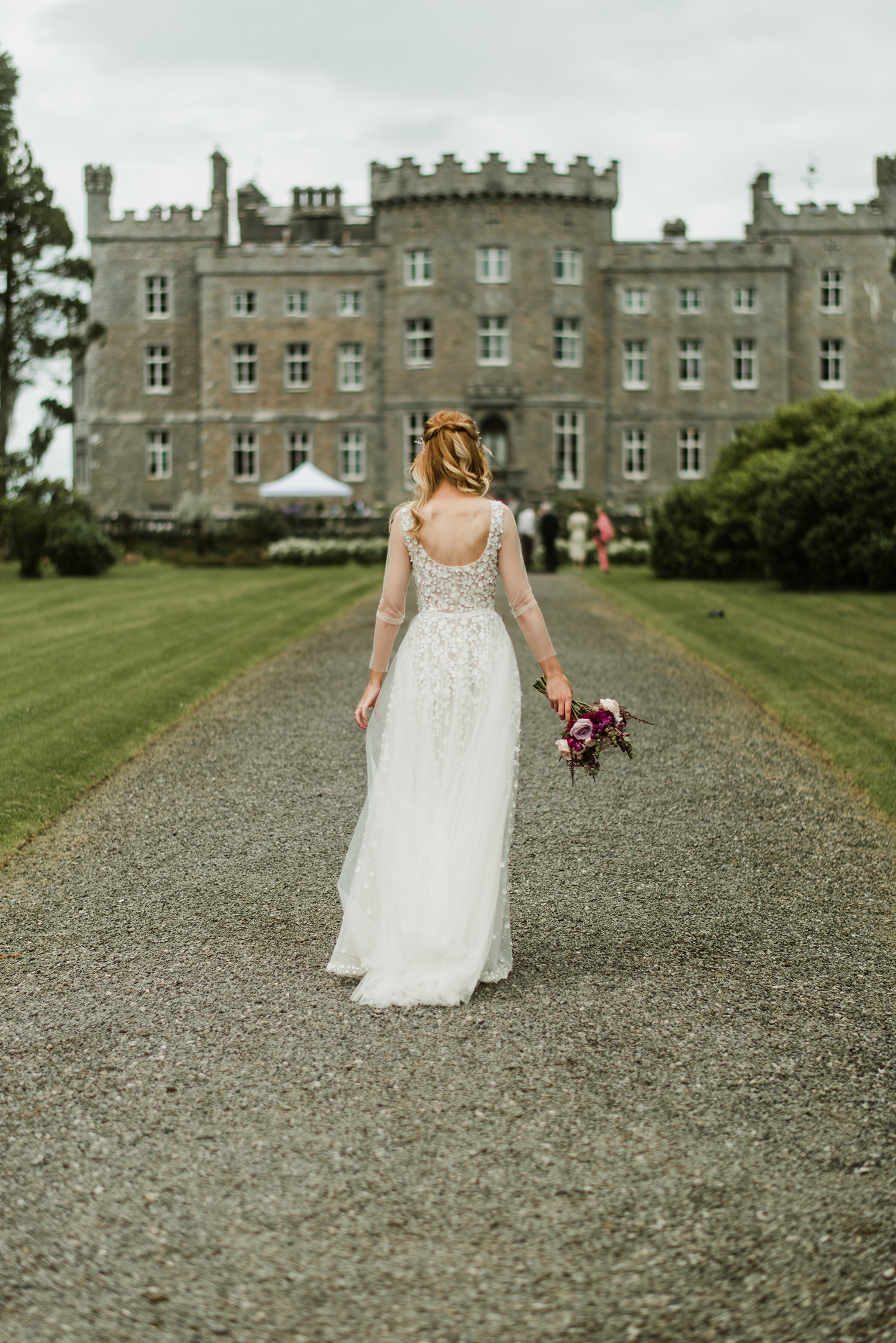 bride walking in direction to castle