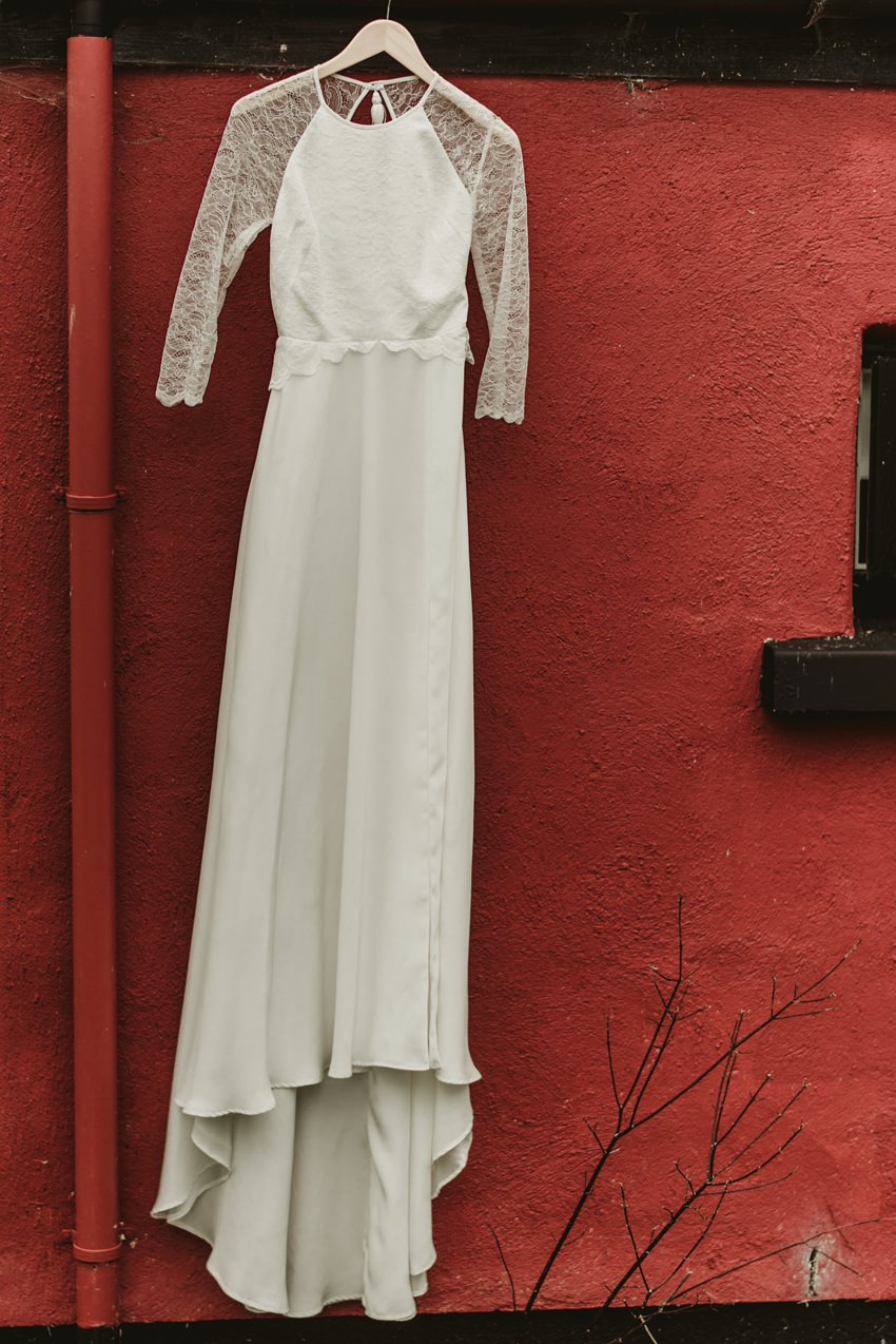 wedding dress hang on red wall of the house