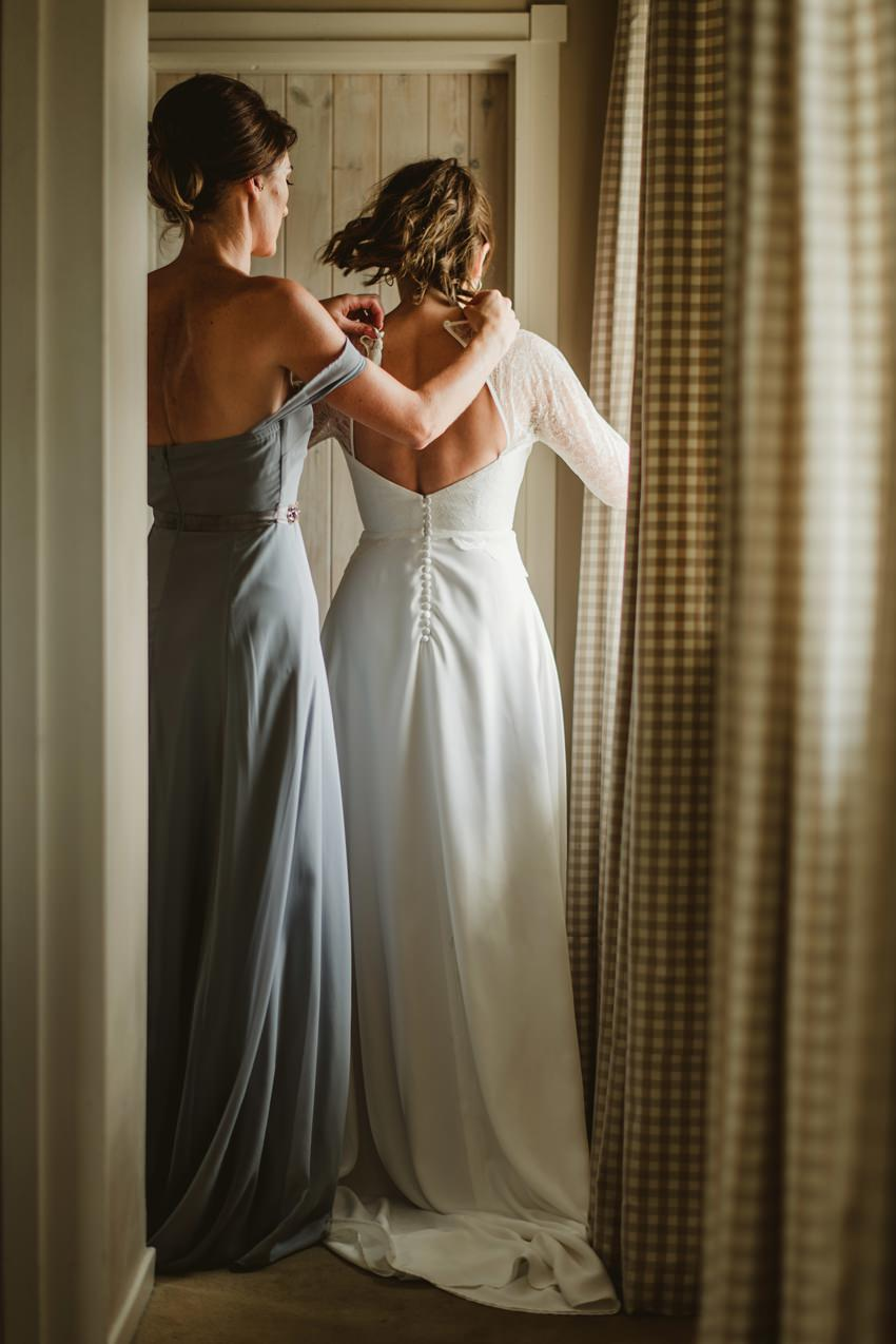 bridesmaid help bride to zip the dress