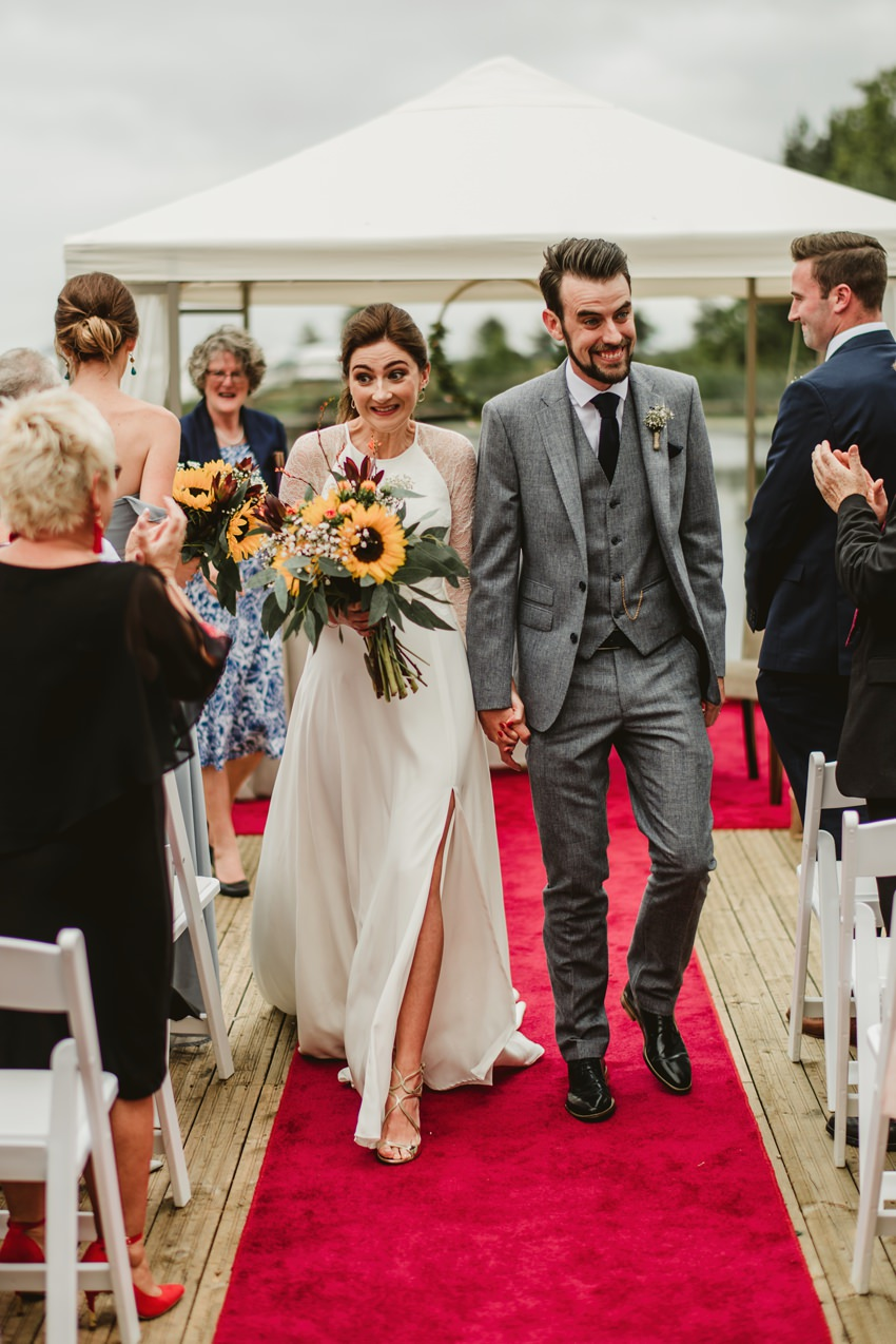 bride and groom walk on red carpet after ceremony