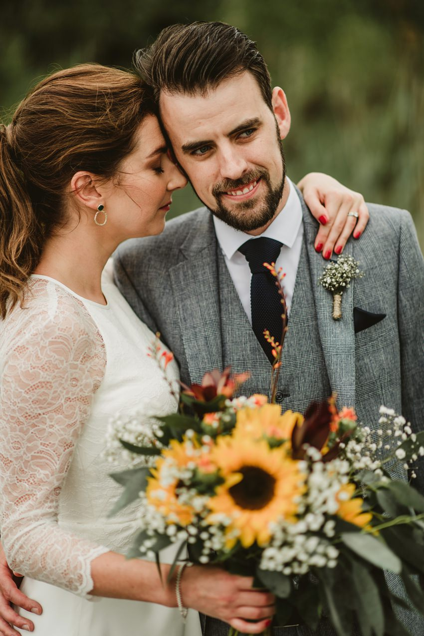 bride and groom with sunflowers  bouquet