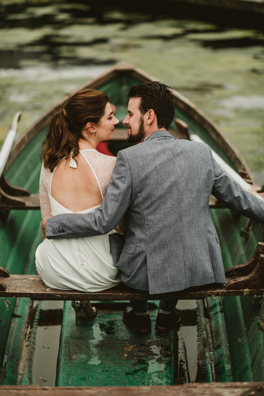 back wiev of bride and groom sitting on wooden green boat