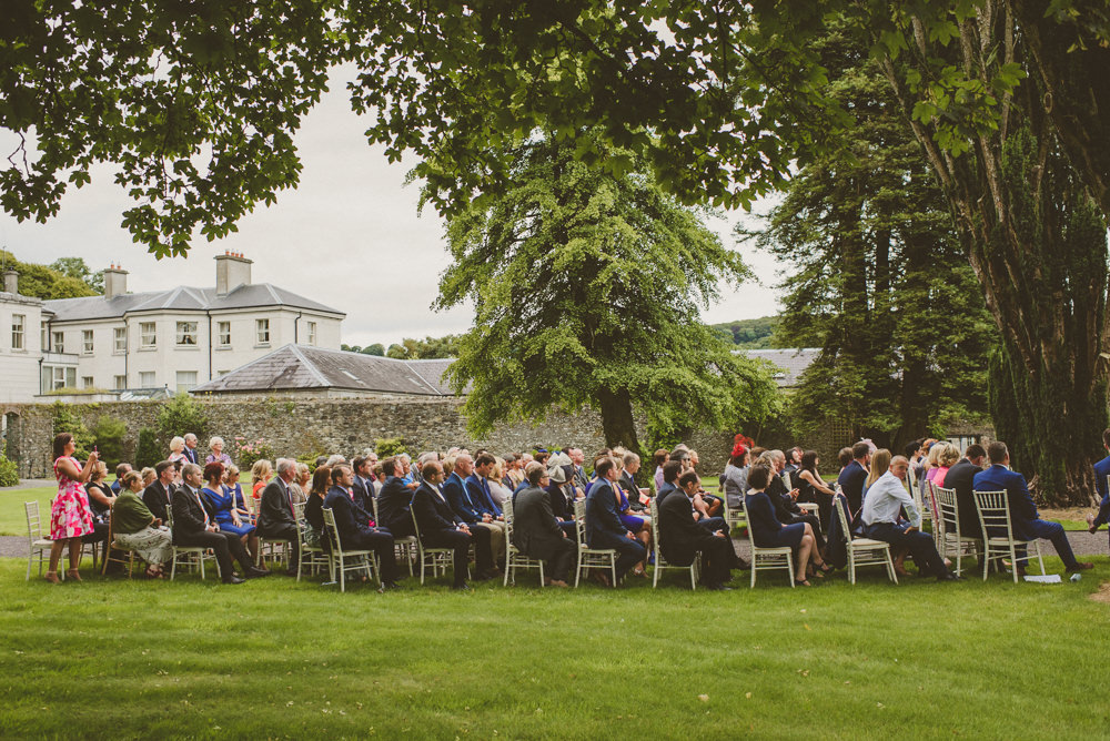 outdoor wedding ceremony on grass fields at front entrance to tankardstown house co,meath